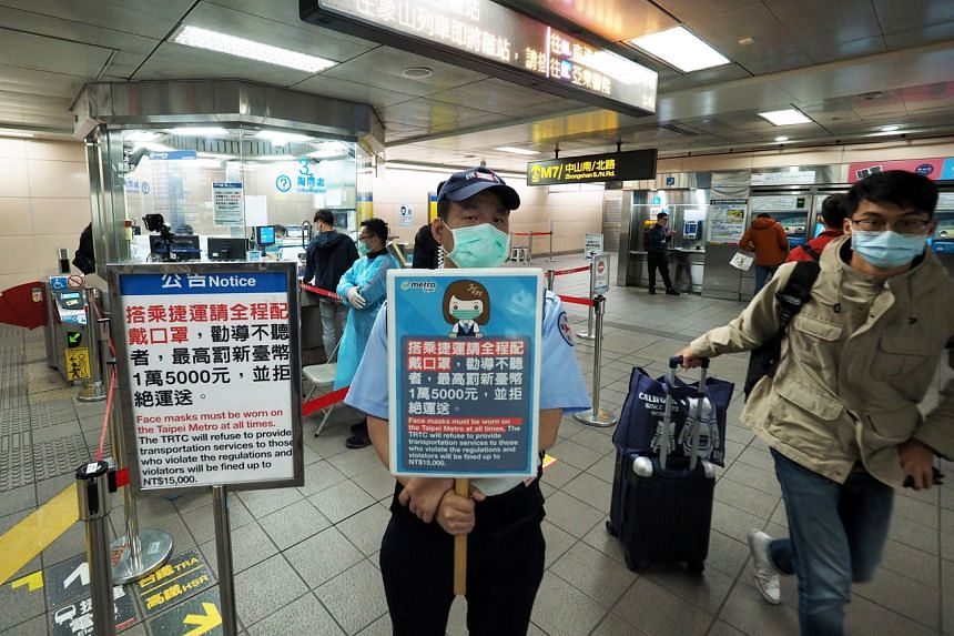 A man holds a sign in Chinese and English saying that passengers must wear masks or face a fine, at a train station in Taipei.