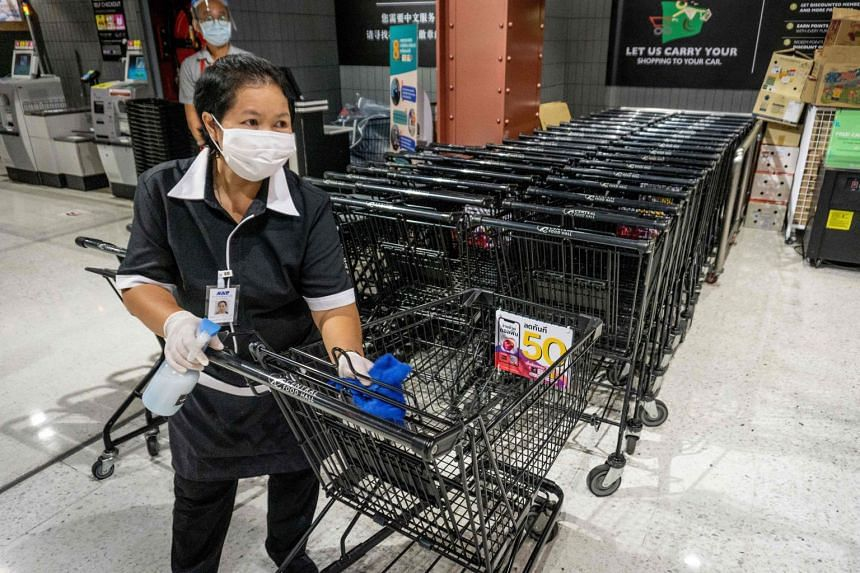 A supermarket employee in Bangkok disinfecting trolleys. Supermarkets, pharmacies and banks in Thailand remain open amid a lockdown to curb the spread of the coronavirus.