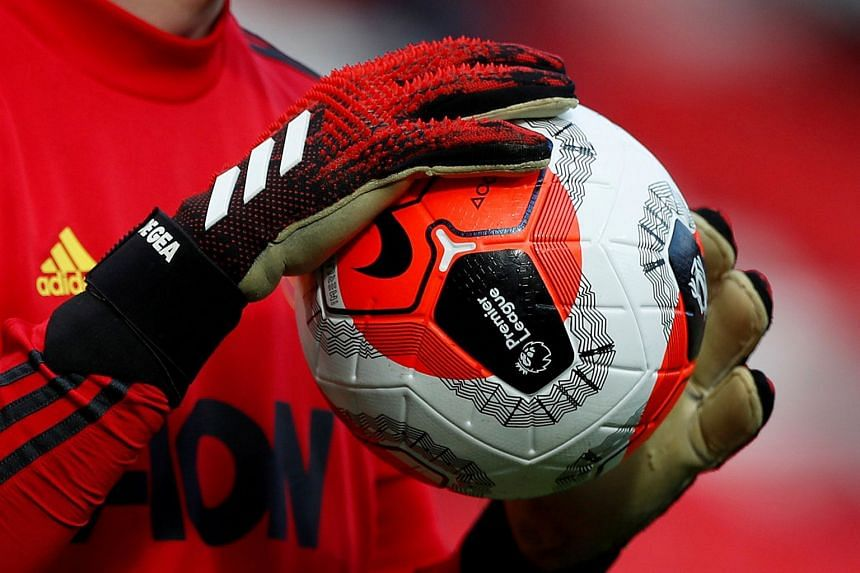 General view of a match ball held by Manchester United's David de Gea during a warm-up.