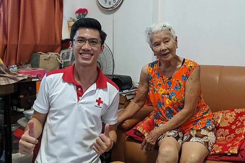 """Above: A member of the Singapore Red Cross visiting Madam Nellie Woo, 83, at her flat last week. Below: Former sweeper Koh Ah Chew (right, on steps), 70, with a neighbour sitting 2m away from him at Chinatown Complex on Thursday. He said: """"How is it"""