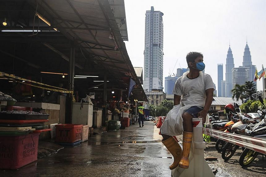 A vendor waiting for customers at a wet market in Kuala Lumpur yesterday. Malaysia entered its 24th day under the movement control order yesterday, which allows people to leave their homes only to buy groceries, medicine or food, or to carry out esse