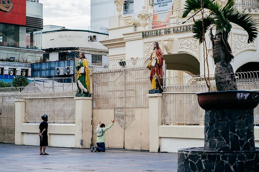 Devotees outside the closed gates of Quiapo Church in Manila yesterday, which was Good Friday. Across the Philippines, churches and shrines are shut and empty because of the sweeping lockdown that aims to keep the spread of the coronavirus in check.