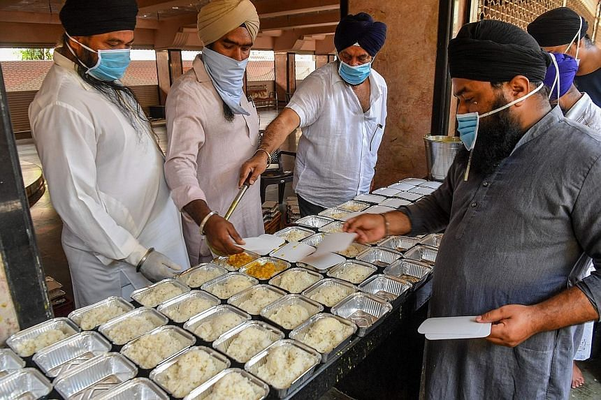 Sikh community volunteers preparing food to be distributed at a temple in Mumbai. Across India, people are coming together to help feed the poor and less privileged. PHOTO: AGENCE FRANCE-PRESSE Labourers and daily-wage workers waiting to receive food