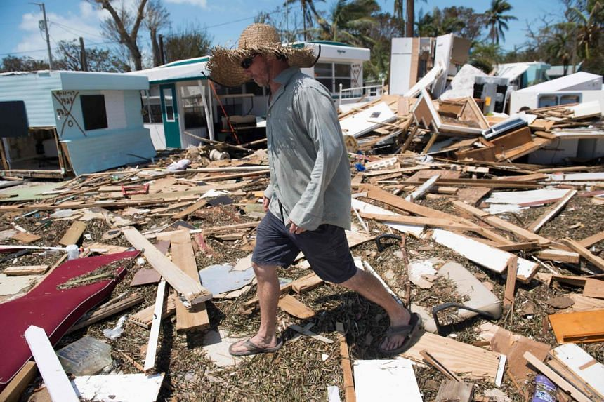 A photo taken on Oct 13, 2018 shows a woman recovering belongings from a house damaged by Hurricane Michael in Florida.