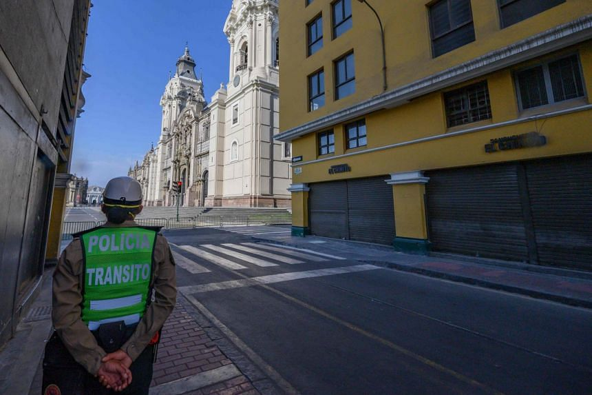 A police woman patrols the streets adjacent to Lima's main square, the Plaza de Armas, on April 9, 2020.