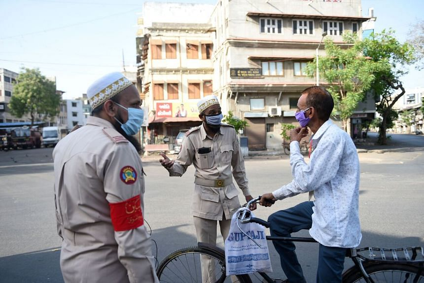 Volunteers in in Ahmedabad speaking with a man on April 10, 2020, amid India's lockdown.
