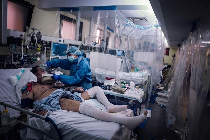 A medical staff member takes care of an intensive care patient infected with Covid-19 in Paris.