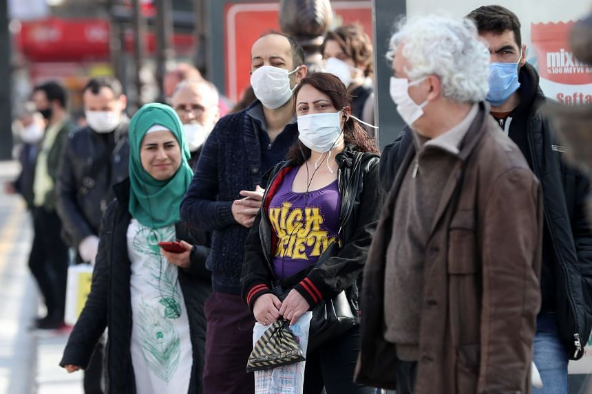 People wearing protective masks wait at a bus stop in Ankara, on April 6, 2020.