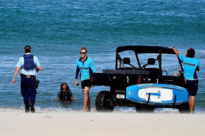 A police officer telling a woman to get out of the water at Sydney's Bondi Beach yesterday. The beach has been closed as part of measures to rein in the spread of the coronavirus. Social distancing rules vary across Australia's states and have caused