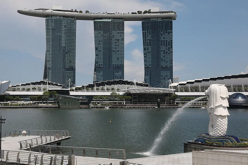 Tourists at the Merlion Park (left) in July last year, with Marina Bay Sands in the background, and what the area looked like on the second day of the circuit breaker in Singapore earlier this month. To contain the spread of the coronavirus, many cou
