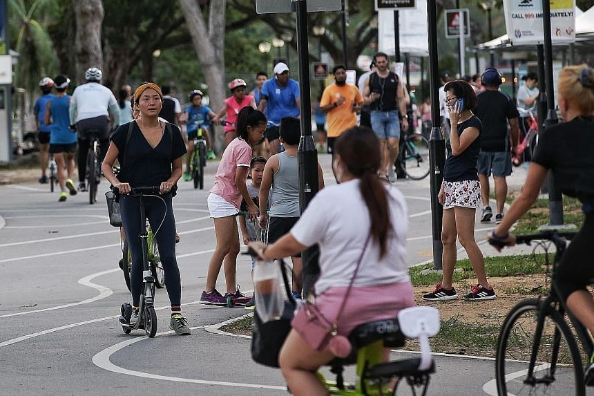 National Parks Board officers dispersing a group of people at Labrador Park at 6pm yesterday. Cyclists and joggers joined people out for a walk in East Coast Park yesterday. Even though most kept some form of social distancing, a number of them were