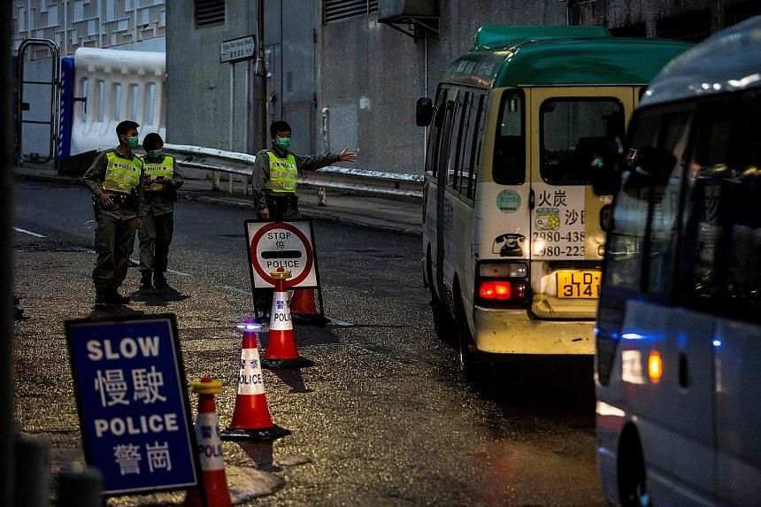 Police manning a road block before local residents arrived at Chun Yeung estate in Hong Kong to begin their 14 days of quarantine on March 4. Hong Kong officers face a unique challenge as they battle the pandemic amid simmering social discontent, wit