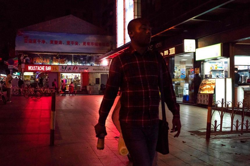 """A March 2018 photo shows people walking in the """"Little Africa"""" district of Guangzhou."""