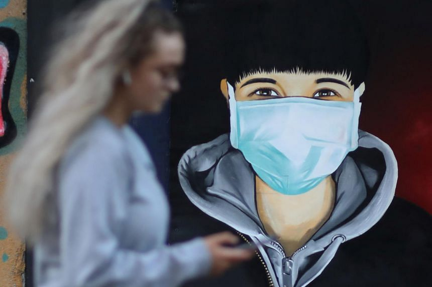 A woman walks past a mural depicting a man wearing a face mask in Sale, Britain, on April 11, 2020.
