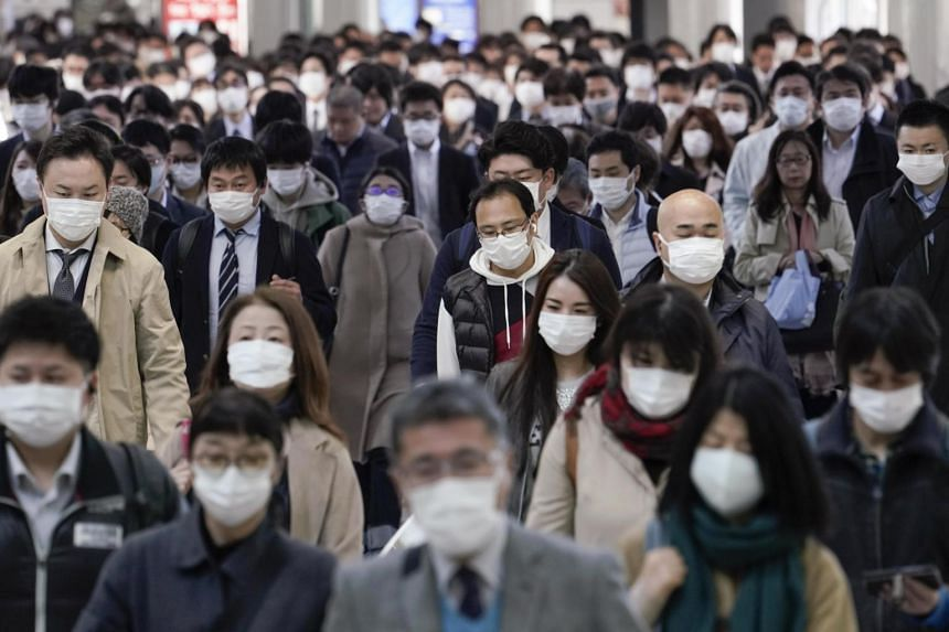 Office workers wearing protective masks as they walk to their offices, at a railway station in central Tokyo, Japan, on April 6, 2020.