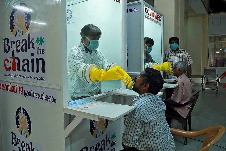 Staff from a medical college collecting swabs from people last week to test for the coronavirus at a walk-in sample kiosk in India's southern state of Kerala. Healthcare workers, who are on the front lines of the fight against Covid-19, increasingly