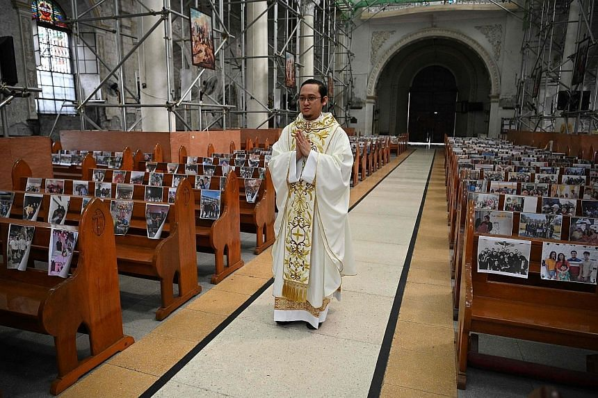 Reverend Father Mark de Leon walking down the aisle in an empty Holy Rosary Parish Church at the start of a procession for Easter Mass in Angeles City in the Philippines' Pampanga province yesterday. In place of parishioners who were not present due