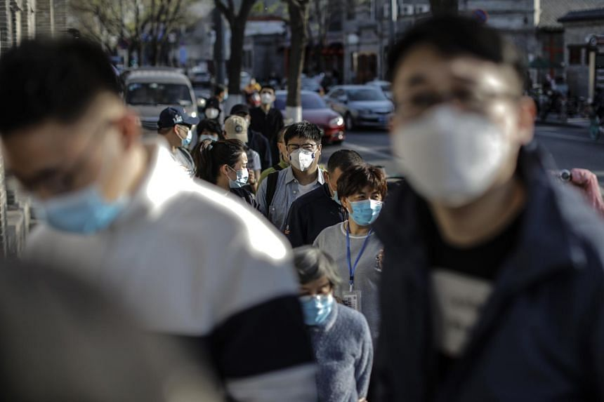 People wearing protective face masks queue outside of a store in Beijing on April 12, 2020.