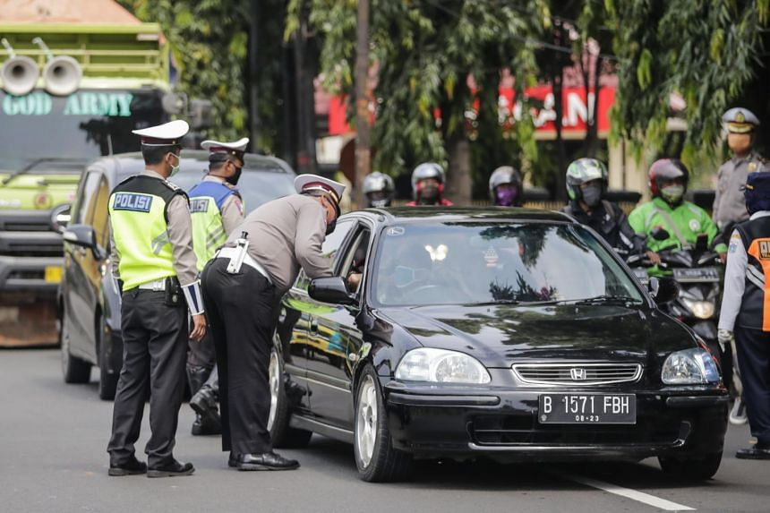 Indonesian police officers stand guard at a checkpoint in Jakarta on April 10, 2020.