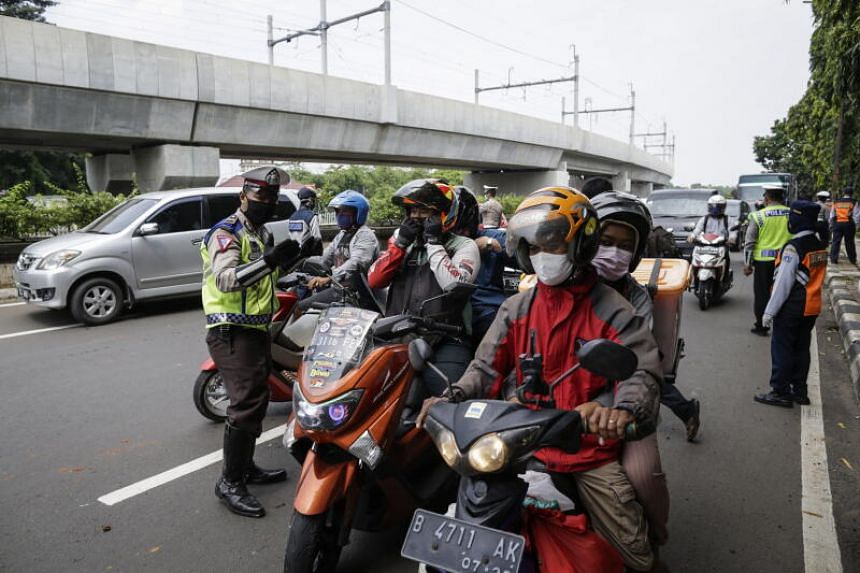 An Indonesian police officer inspects motorists at a checkpoint in Jakarta, on April 10, 2020.