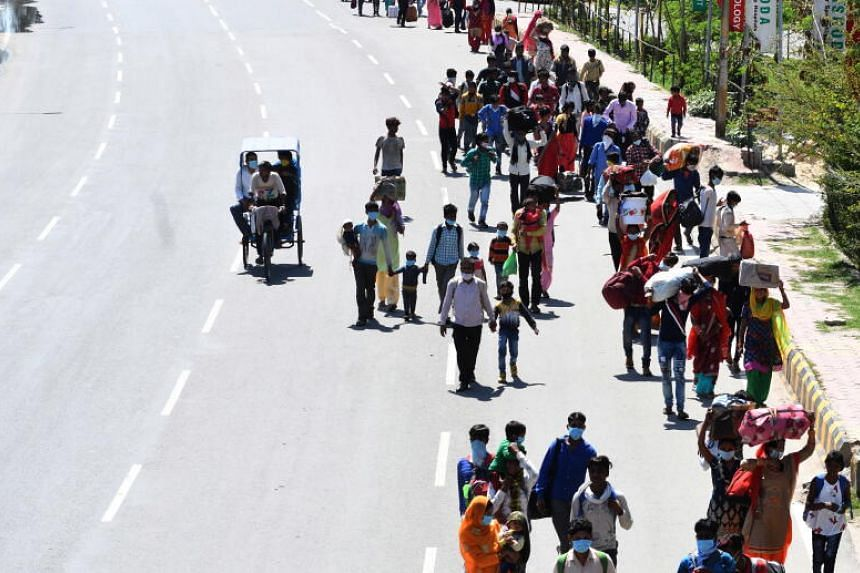 Indian migrant workers make the long walk home to their villages from New Delhi on March 28, 2020.