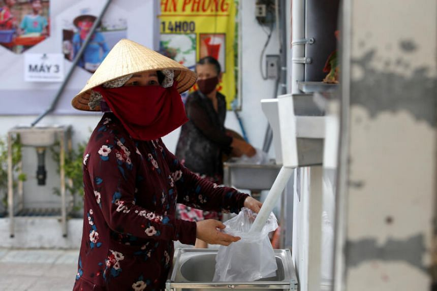 A woman fills a plastic bag with rice from a 24/7 automatic rice dispensing machine in Ho Chi Minh on April 11, 2020.