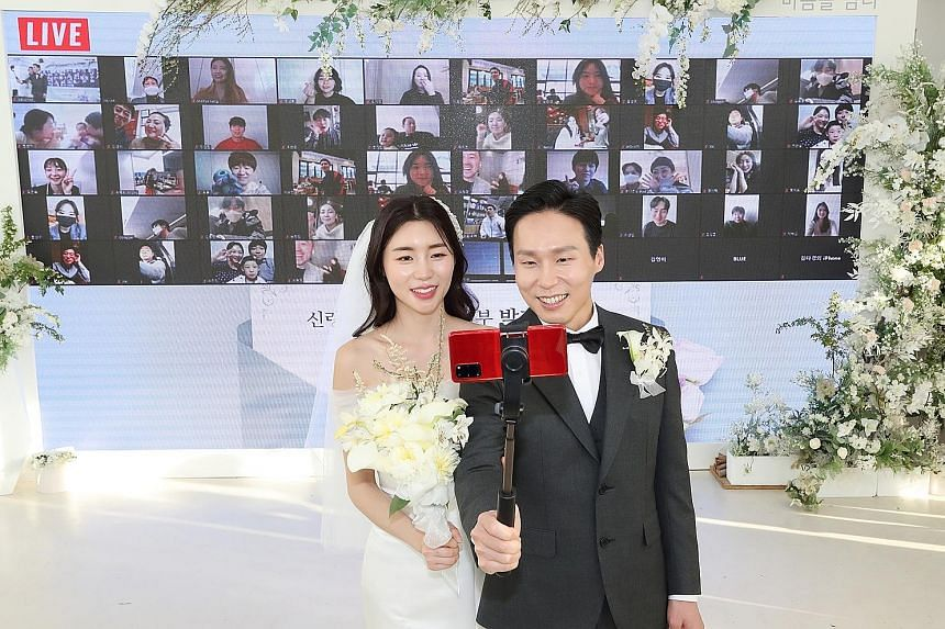 Groom Ha Ji-soo and bride Park Ji-ye posing for a wefie as they live-streamed their wedding from Seoul on April 4, with family and friends (background) logged on to watch and interact with the couple.