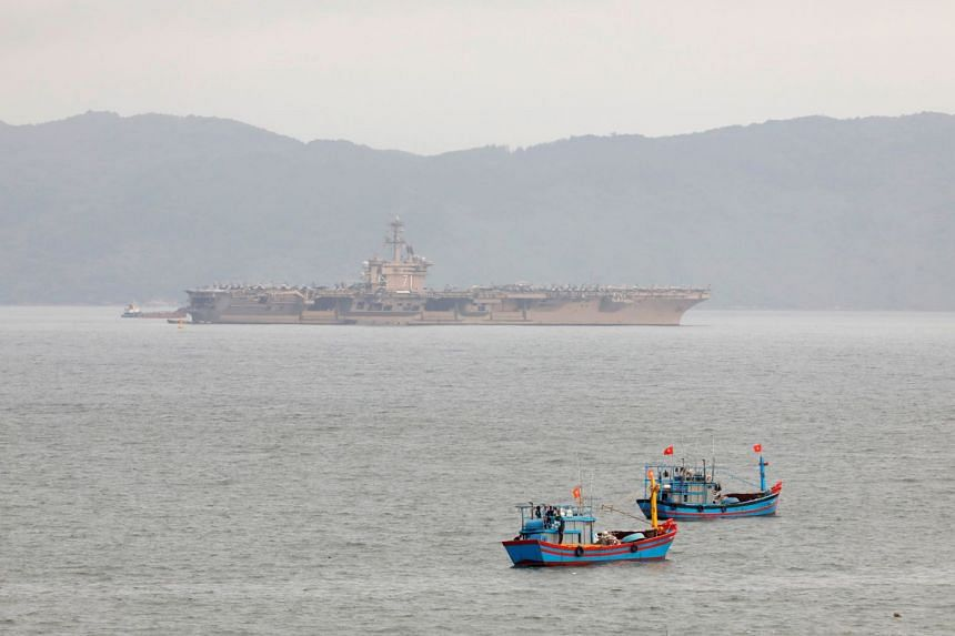 The USS Theodore Roosevelt (CVN-71) is seen near Vietnamese fishing boats at a port in Danang city, Vietnam, on  March 6, 2020.