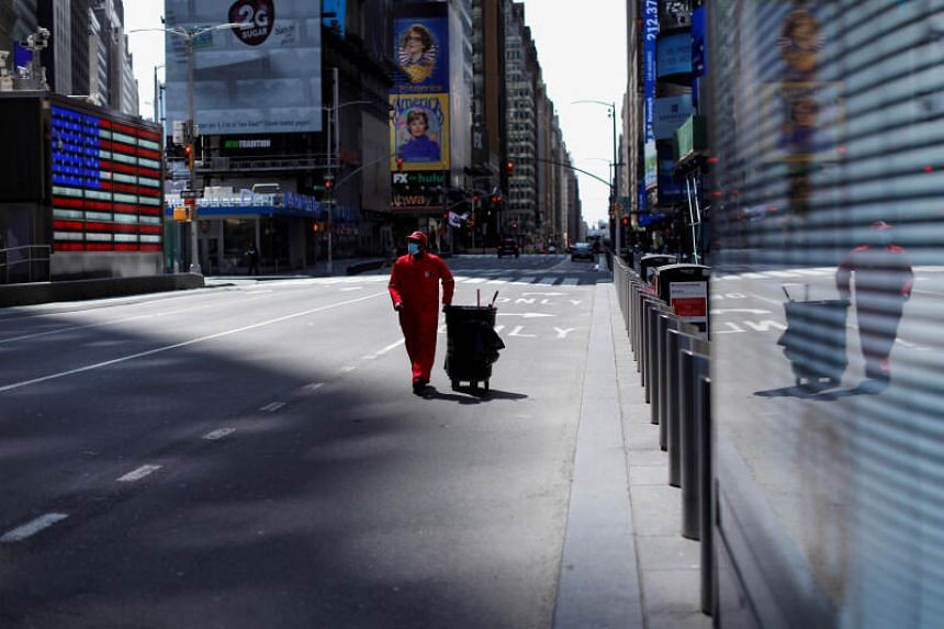 A worker walks though a nearly empty Times Square in New York City.