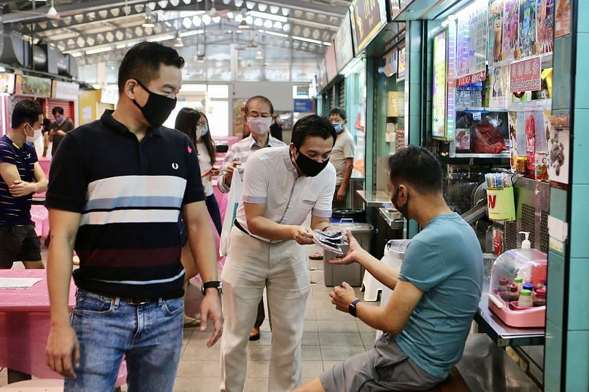 Tanjong Pagar GRC MP Chia Shi-Lu distributing reusable face masks to a hawker at Alexandra Village Food Centre on Sunday. With him is Colonel Eric Chua (in striped T-shirt).