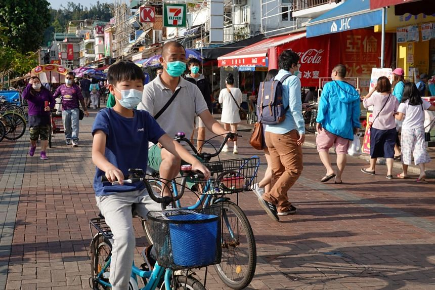 People wearing face masks are seen at Cheung Chau island in Hong Kong on April 12, 2020.