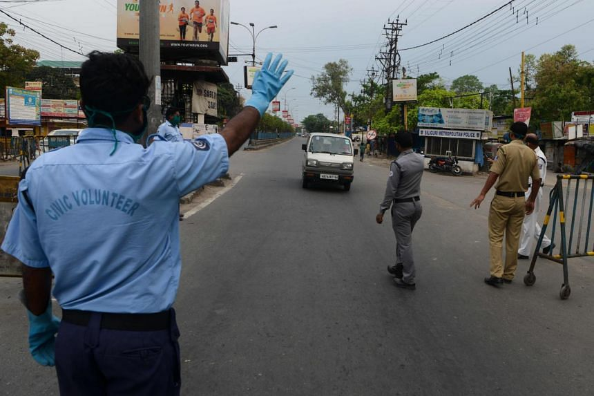 Police personnel and civic volunteers stop a vehicle at a checkpoint during a government-imposed nationwide lockdown, in Siliguri on April 13, 2020.