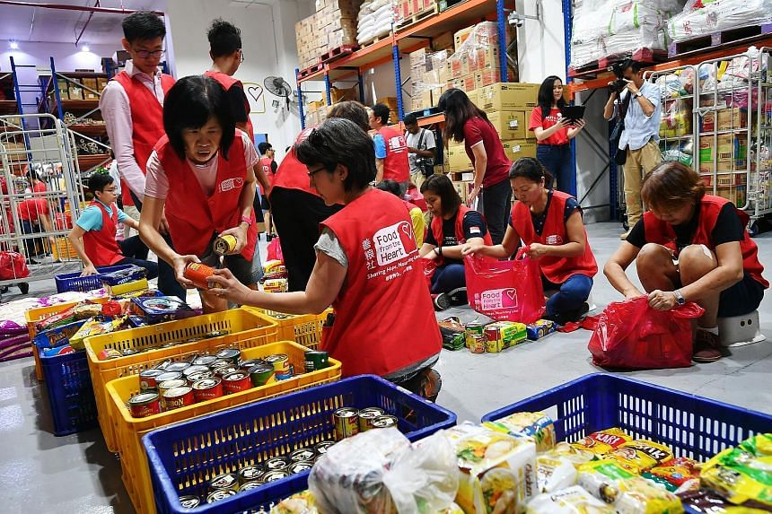 Volunteers helping to pack food at Food from the Heart in February. Minister for Social and Family Development Desmond Lee on Monday said many social service agencies and volunteer groups have asked if they can continue with their community service o