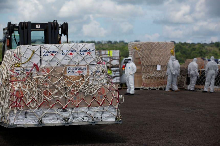 Royal Australian Air Force personnel unload palettes of humanitarian aid at Port Vila airport in Vanuatu, on April 13, 2020.