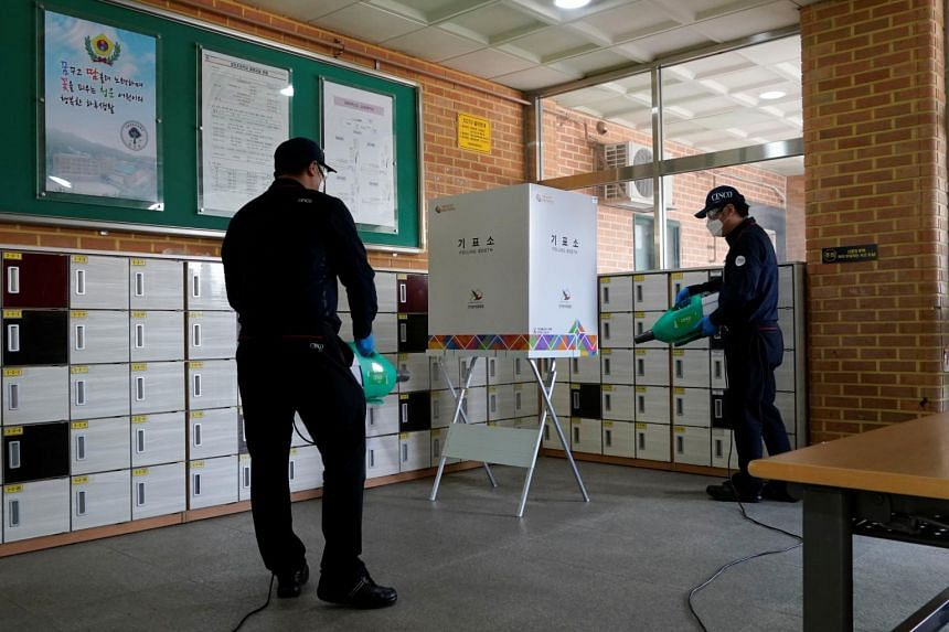 Employees from a disinfection service company sanitise a polling booth in Seoul, South Korea, on April 14, 2020.