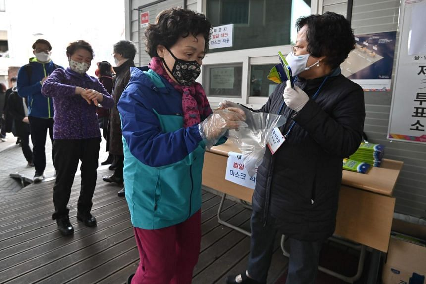 A woman wears plastic gloves before casting her ballot at a polling station in Seoul on April 15, 2020.