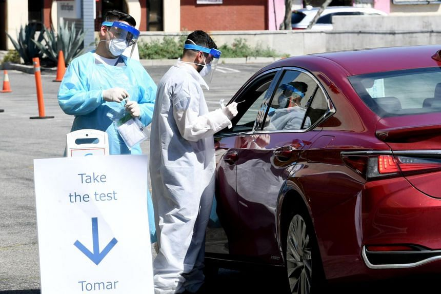 Workers gather the tests administered as Mend Urgent Care hosts a drive-thru testing for the virus, on April 14, 2020.