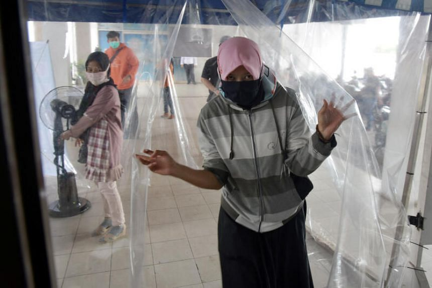 A woman leaves a disinfection chamber in Pekanbaru, Indonesia, on April 6, 2020.