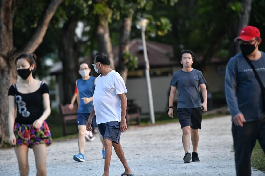 """Joggers and walkers at Bedok Reservoir Park on April 15, 2020, at around 6pm. Some are wearing masks while others are not, even though it is mandatory except for those engaged in """"strenuous exercise""""."""