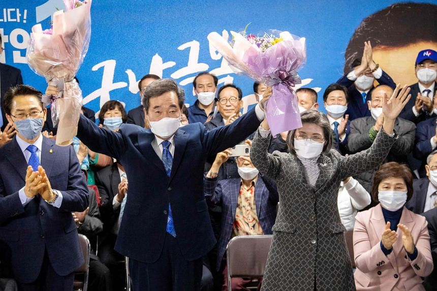 South Korea's former prime minister and candidate of the ruling Democratic Party  Lee Nak-yon (left), and his wife Kim Suk-hee hold flowers in a sign of victory, on April 15, 2020.