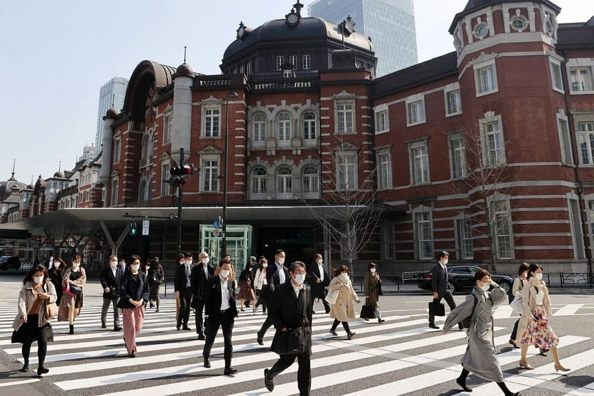 People wearing face masks cross a street outside Tokyo Station, on April 8, 2020.