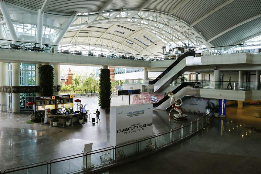 A traveller walks through a nearly empty international arrivals terminal of Gusti Ngurah Rai airport in Bali, on April 1, 2020.