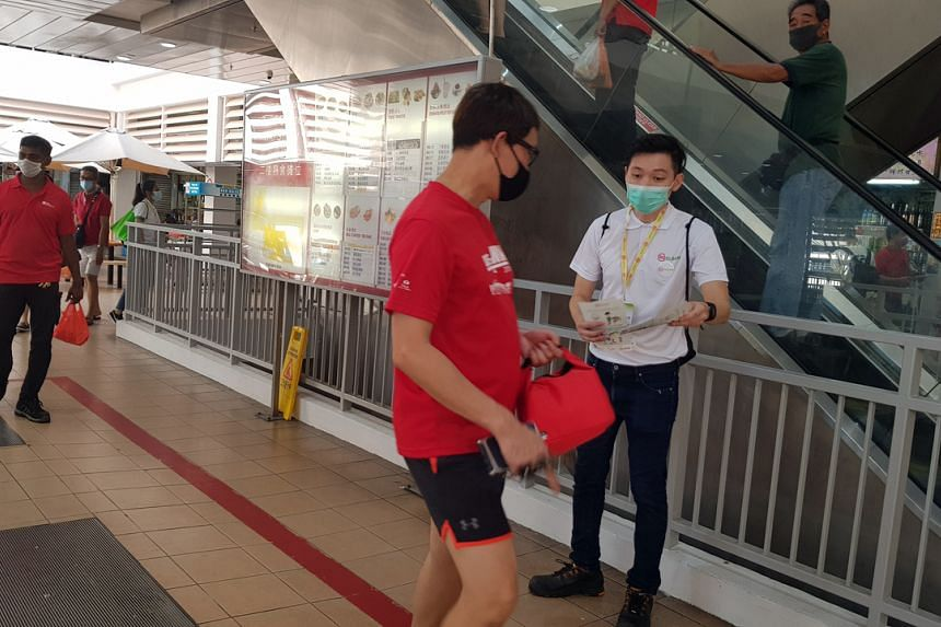 Mr Darren Ang, an SG Clean Ambassador, distributes fliers to members of the public.