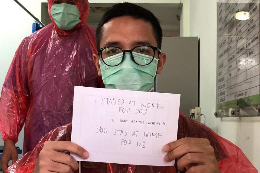 Dr Muhammad Farras Hadyan (front) holds a sign while wearing a red raincoat as a protective suit in Jakarta.