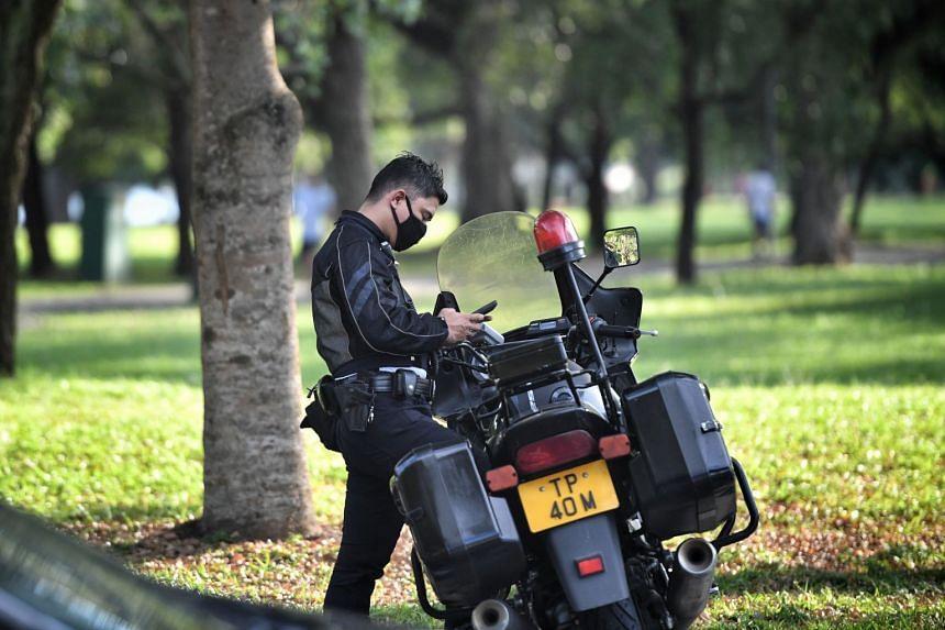 A traffic police officer wearing a face mask is seen at Bedok Reservoir Park carpark.