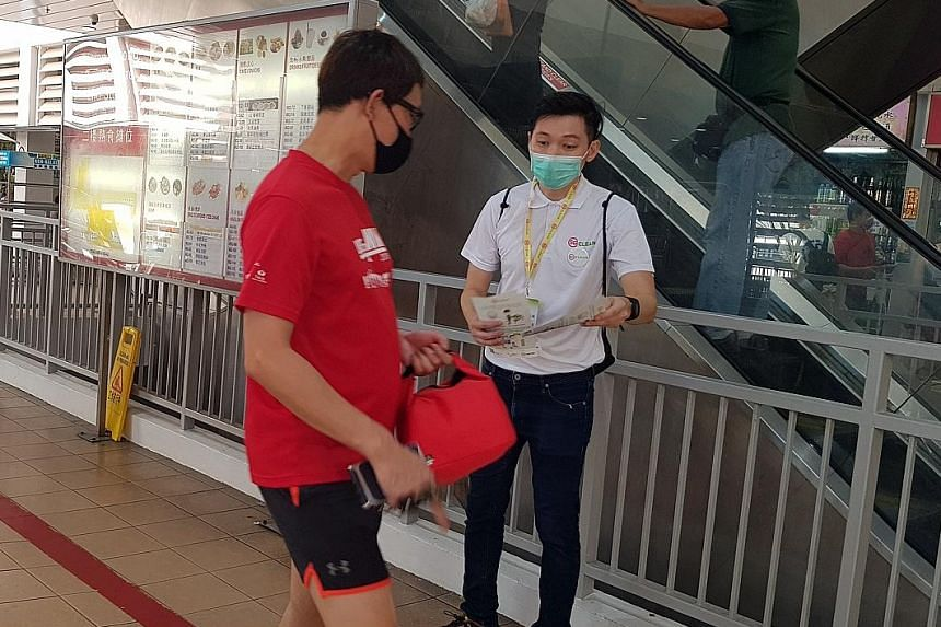 """Mr Darren Ang, seen here giving out pamphlets to members of the public, said of his efforts as an SG Clean ambassador: """"I don't see it as work - I see it as a very important mission."""" PHOTO: NATIONAL ENVIRONMENT AGENCY"""