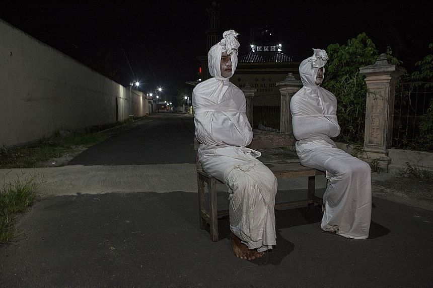 """Volunteers dressed as """"pocong"""", or shroud ghosts, in a bid to urge people to stay home amid the coronavirus outbreak in a village in Sukoharjo, Central Java. Indonesia yesterday reported 27 more deaths from the virus, which has now claimed close to 5"""