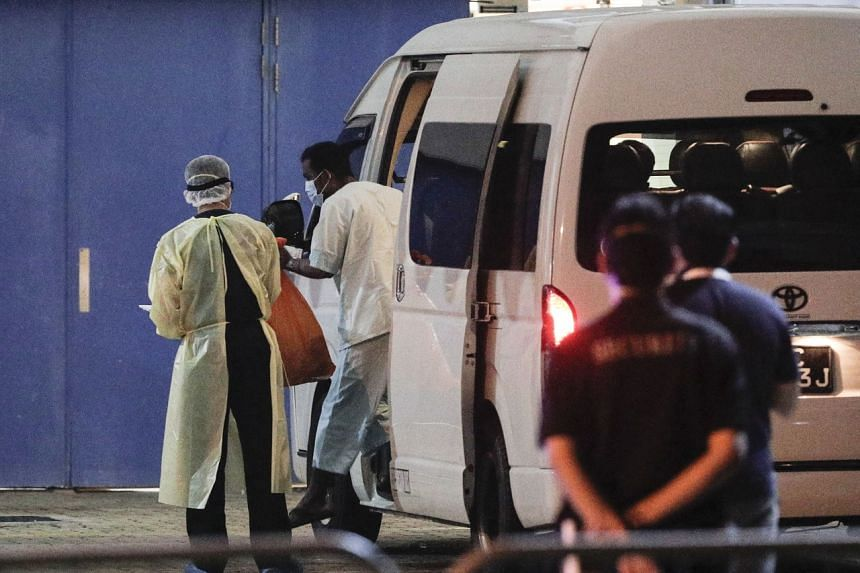 A man believed to be a recovering Covid-19 patient, exits a van at the Singapore Expo community isolation facility on April 10, 2020.
