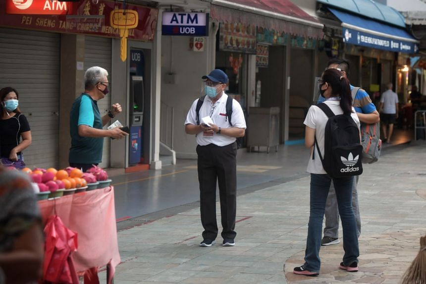 Enforcement officers from the Singapore Food Agency speaking to a resident at the Toa Payoh West Market and Food Centre on April 15, 2020.