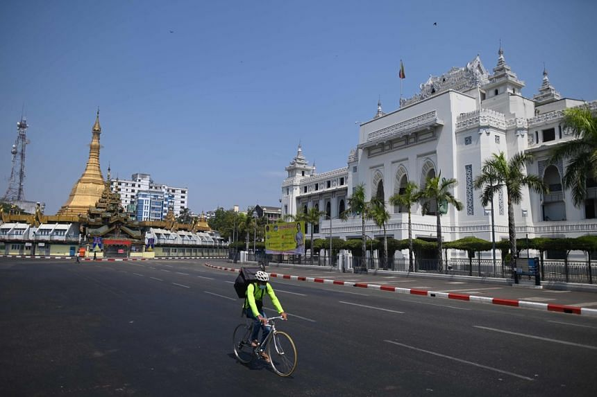 A man cycles along an empty street on the first day of Myanmar's New Year in Yangon on April 12, 2020.